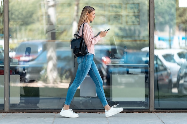 대학 캠퍼스를 걷는 동안 스마트폰을 사용하는 아름다운 금발 여학생의 사진.