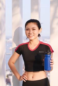 水のボトルを保持している美しい女性ランナーのショット。屋外でトレーニングを実行した後、休憩を取るフィットネス女性。