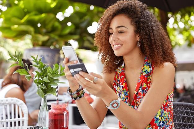 アフロの髪型を持つ美しいうれしそうな若い女性のショット、スマートフォンでクレジットカードの数を入力、オンラインで購入、または銀行口座をチェック