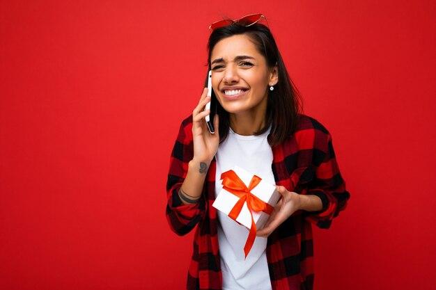 身に着けている赤い背景の壁の上に分離された美しい幸せな感情的な若いブルネットの女性のショット