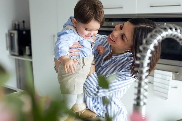 집에서 부엌에서 노는 아기와 함께 아름다운 어머니의 사진.
