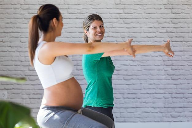 Выстрел красивой беременной женщины с ее физиотерапевтом, делающим упражнения пилатеса, готовящиеся к родам.