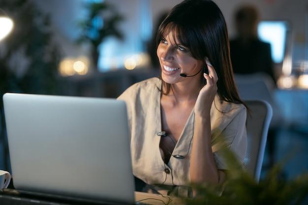 オフィスに座っているイヤホンと話している間ラップトップで作業している美しい笑顔の若いビジネス女性のショット。