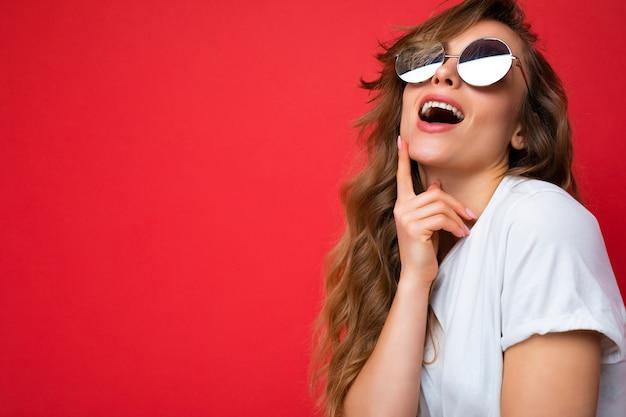 아름 다운 생각 젊은 어두운 금발 곱슬 여자의 총 빨간색 배경 위에 절연