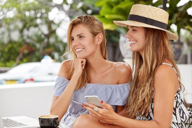 Снимок: красивые женщины отдыхают в уютном ресторане, используют современные технологии для совершения покупок в интернете, радостно смотрят на портативный компьютер, используют кредитную карту для оплаты покупок, рады выпить кофе