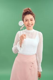 Выстрел из красивой молодой азиатской женщины. красивая девушка держит круглые конфеты и весело улыбается. изолированный зеленый фон
