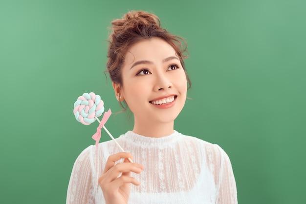 美しい若いアジアの女性のショット。丸いキャンディーを持って元気に笑っているかわいい女の子。孤立した緑の背景