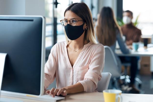 Выстрел красивой молодой деловой женщины в гигиенической маске, работающей с компьютером, сидя за столом в современном офисе запуска.