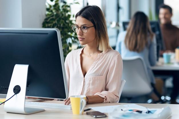 現代のスタートアップオフィスの机に座ってコンピューターで作業している美しい若いビジネス女性のショット。 Premium写真
