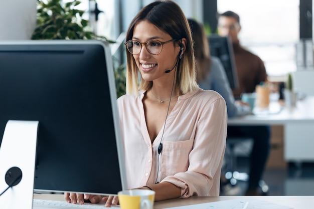 Выстрел красивой молодой деловой женщины, работающей с компьютером во время разговора с наушником, сидя в современном офисе запуска.