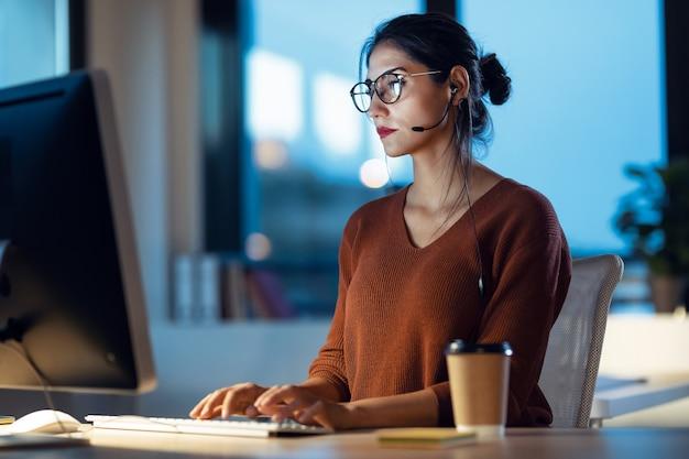 オフィスに座っているイヤホンと話しながらコンピューターで作業している美しい若いビジネス女性のショット。