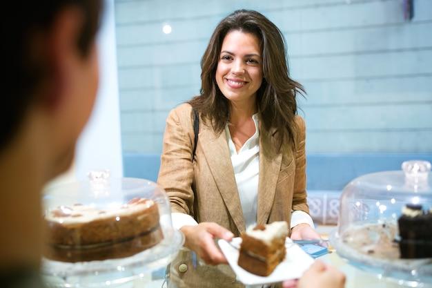 커피숍에서 맛있는 집에서 만든 당근 케이크의 일부를 사는 아름다운 젊은 여성 사업가의 총.