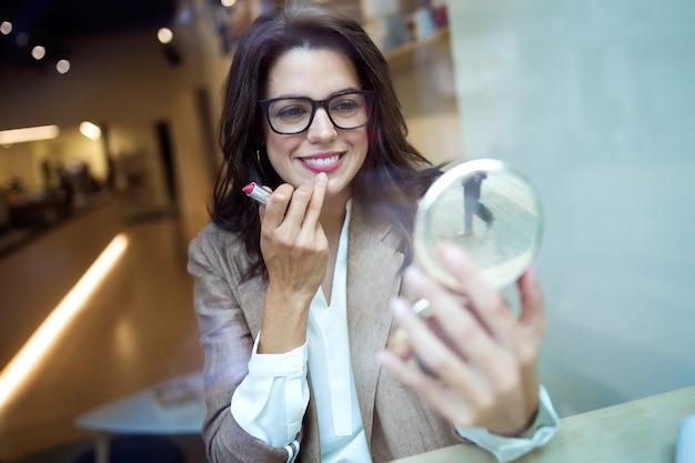 거울을 보고 커피숍에서 립스틱을 바르는 아름다운 젊은 여성 사업가의 총.