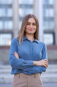 腕を組んで通りの建物に立っている間青いシフォンシャツを着ている美しい若い実業家のショット。