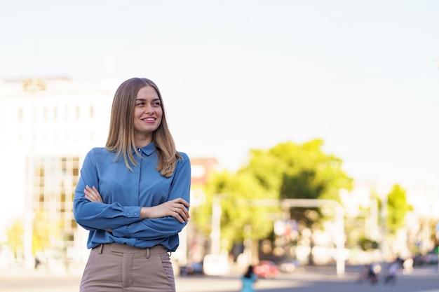 腕を組んで通りに立っている間青いシフォンシャツを着ている美しい若い実業家のショット。