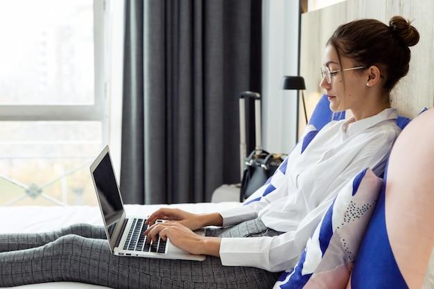 ホテルの部屋のベッドに横たわっている彼女のラップトップで作業している美しい若い実業家のショット。