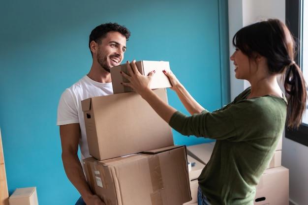 新しい家に移動しながら段ボール箱を保持している美しい若いカップルのショット。
