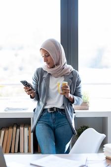 사무실 창문 옆에 서 있는 동안 스마트 폰을 사용하여 히잡을 쓴 아름다운 젊은 이슬람 사업가의 사진.