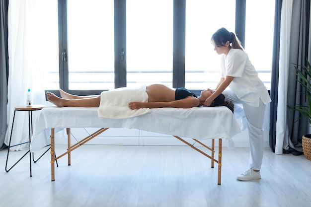 집에 있는 들것에 임신한 여성의 목에 정골 또는 척추 교정 치료를 하는 아름다운 젊은 물리치료사의 총.