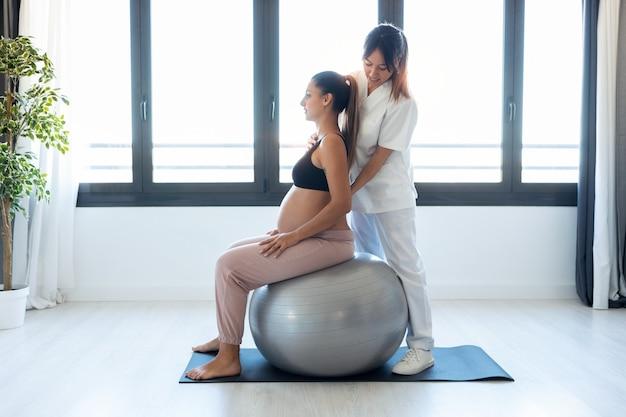 Выстрел красивого молодого физиотерапевта, помогающего красивой беременной женщине делать упражнения пилатеса с мячом, готовясь к родам в домашних условиях.