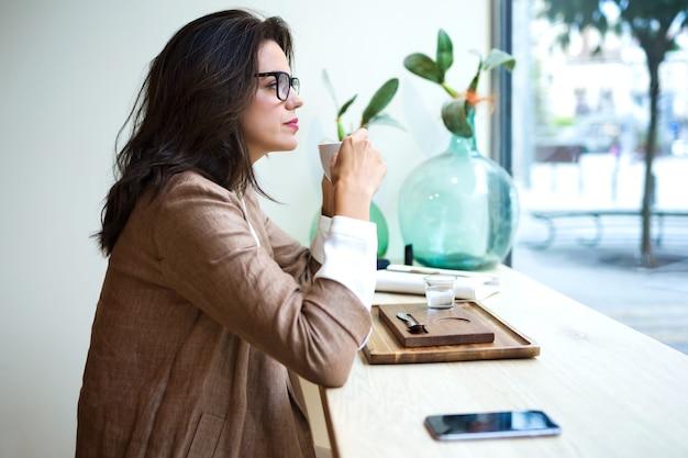Выстрел красивой молодой женщины, пьющей латте зеленого чая матча на деревянном столе в кафе.