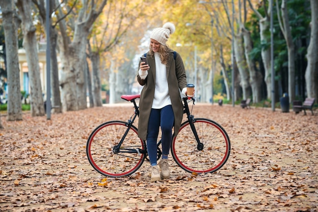 秋の公園をサイクリングしながらスマートフォンでメッセージを送信する美しい若い女性のショット。