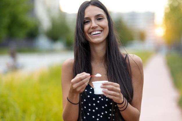 通りに立っているアイスクリームを食べながら笑っている美しい若い女性のショット。