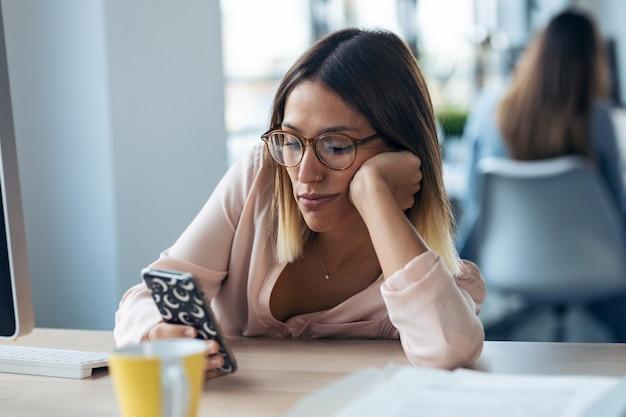 Выстрел скучной молодой деловой женщины, отправляющей сообщения с мобильного телефона, сидя в современном офисе запуска.