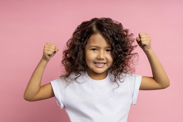 白いtシャツを着て、手を上げて、拳を見せて、力を示して、身を守る準備ができている、巻き毛の髪型の勇敢で強い小さな女の子のショット。感情。