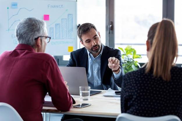 사무실에서 회의하는 동안 회의실에서 함께 토론하는 사업가들의 총.