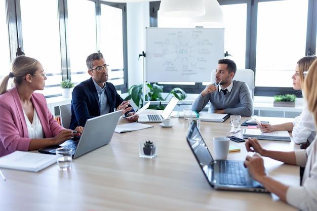 オフィスでの会議中に会議室で一緒に議論しているビジネスマンのショット。