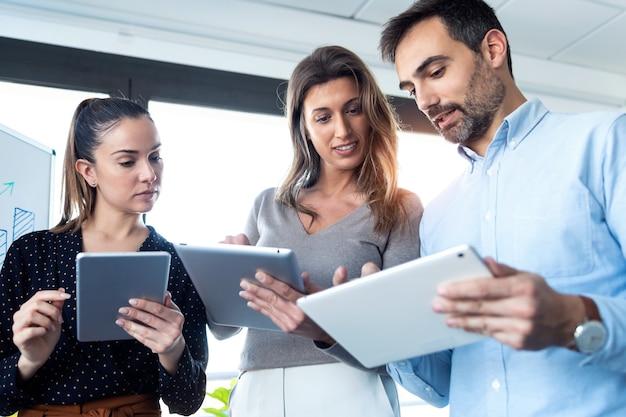 사무실 회의실에서 함께 토론하는 동안 디지털 태블릿으로 작업하는 비즈니스 사람들의 사진.