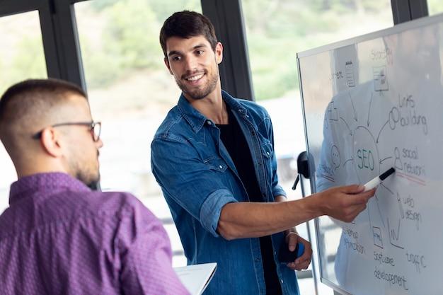 現代のスタートアップオフィスで彼らの新しいプロジェクトの彼の同僚と話している間、ホワイトボードを指しているビジネスの若い男のショット。