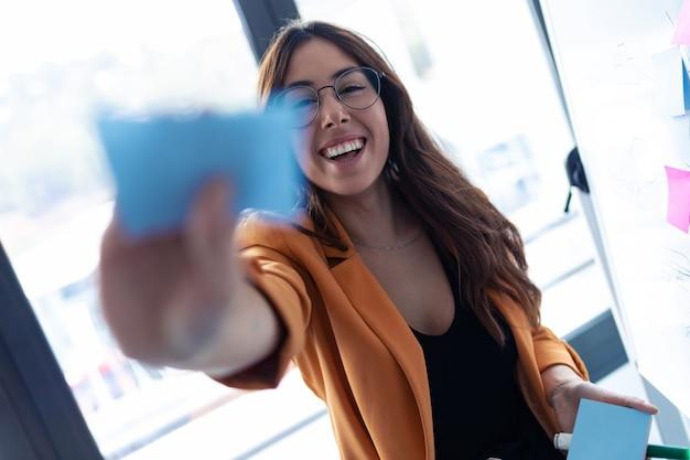 사무실에서 포스트잇 스티커로 작업하는 동안 카메라를 바라보는 비즈니스 젊은 여성의 총.