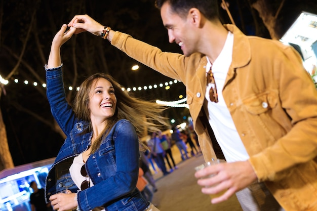 밤에 거리의 먹자 시장에서 손을 잡고 춤을 추는 평온한 젊은 부부의 샷.