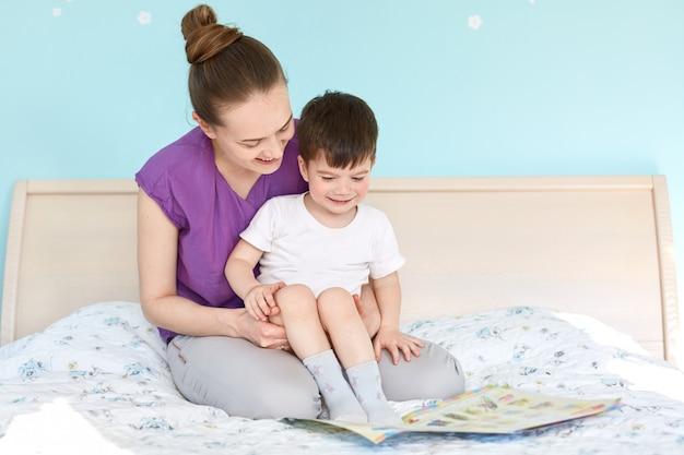 Кадр заботливой матери в декретном отпуске и маленького мальчика, читающего сказку перед сном