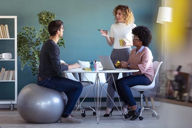 オフィスで一緒に働いて新しいプロジェクトについて話しているカジュアルな若いビジネスマンのショット。