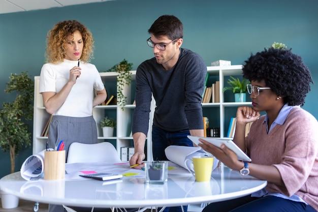 カジュアルな若い起業家がオフィスで一緒に働いて新しいビジネスについて話しているショット。