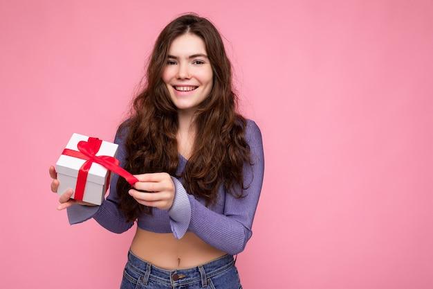 매력적인 긍정적 인 미소 갈색 머리 곱슬 젊은 여자의 총 분홍색 배경 위에 절연