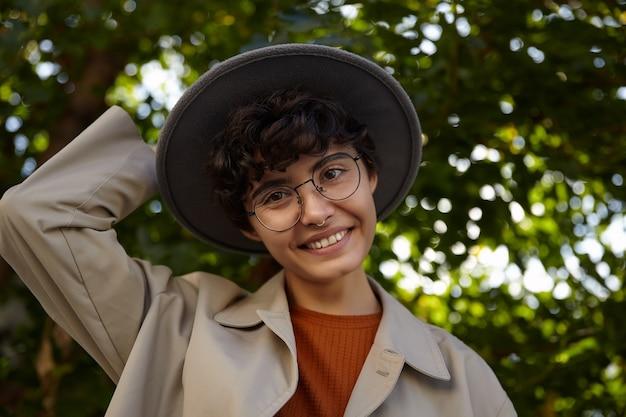 晴れた日に緑の街の公園でポーズをとって、前向きに笑って、彼女の帽子に手を保ちながら、流行の服とアイウェアを身に着けている巻き毛の短い髪の陽気なブルネットのきれいな女性のショット