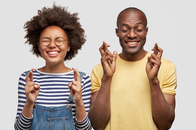 陽気な希望に満ちた暗い肌の女性と男性の学生のショットは指を交差させます