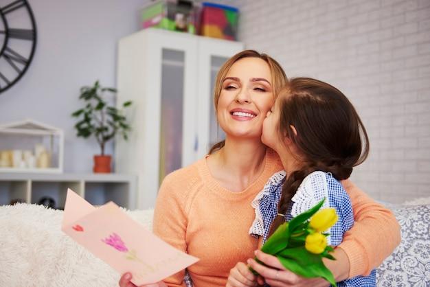 Снимок ребенка, целующего маму в щеку