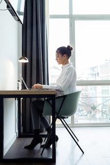 ホテルの部屋の机の上で彼女のラップトップで作業している集中した美しい実業家のショット。
