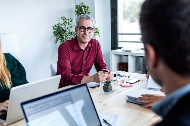 공동 작업 공간에서 그의 파트너를 듣고 집중된 비즈니스 남자의 쐈 어.