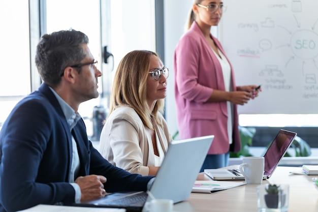 Снимок: сосредоточенная бизнес-команда слушает партнеров и работает с ноутбуком в коворкинге.