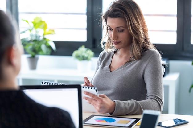 공동 작업 공간에서 회의를 위해 메모를 검토하는 집중된 비즈니스 여성의 샷.