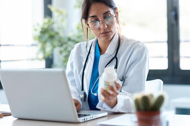 集中した女性医師のショットは、相談でラップトップに処方箋を書きます。