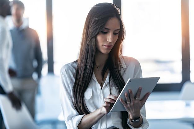 Выстрел сконцентрированной молодой бизнес-леди, использующей свой цифровой планшет, стоя в коворкинге.