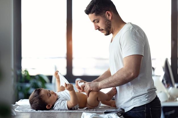 집에 있는 작은 아기에게 기저귀를 갈아주는 집중된 젊은 아버지의 샷.