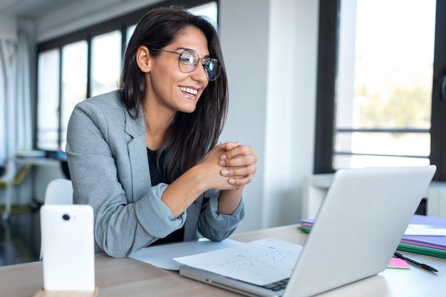 オフィスからラップトップでビデオ会議をしながらウェブカメラを見て話している自信のあるビジネスウーマンのショット。